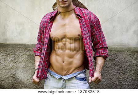 Torso of muscular young man taking off shirt, wearing jeans and straw hat, outdoors against a wall