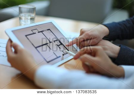 Real-estate agent showing house plans on electronic tablet