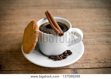 Cup of black coffee with cookie cinnamon stick and coffee beans on old vintage wooden table