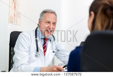Doctor talking to his patient in his office