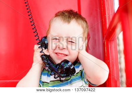 child speaks on the phone in noisy environments. kid hand closed his ears and squeezed his eyes shut while talking on the phone in a red telephone box. noisy surroundings, problem with phone connection