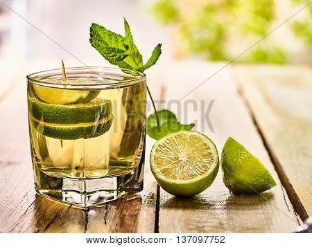 Alcohol drink. On wooden boards is glass with alcohol green transparent drink and half lime . A drink number thirteen cocktail mojito with slice lime and mint leaf. Country life. Light background.