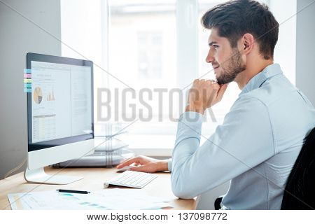 Side view of handsome young smiling businessman in casual cloth sitting at the table and using personal computer in office
