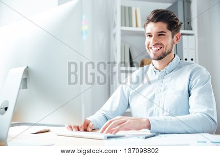 Smiling young happy businessman using laptop computer in office