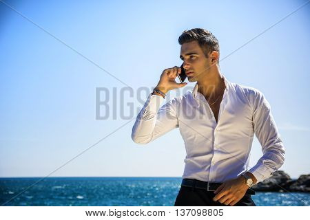 Young man at the seaside talking on cell phone while looking at the sea. Large copyspace