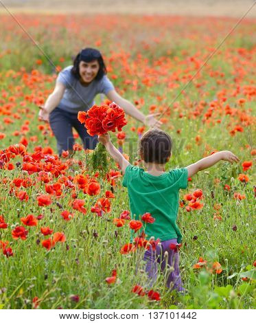 mother and daughter on a poppies fild