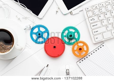 workflow and teamwork concepts with colorful gears different gadgets and office stationery on the white office table