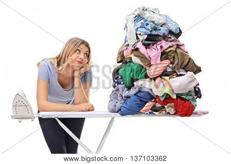 Sad woman leaning on an ironing board and looking at a pile of clothes isolated on white background