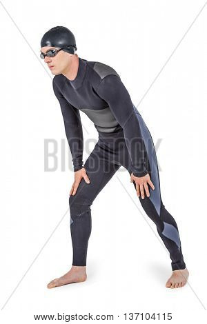 Swimmer in wetsuit and swimming goggles posing on white background