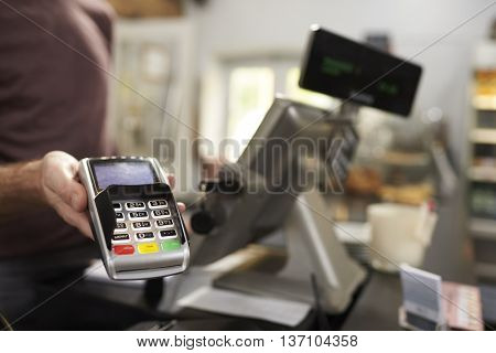 Man behind counter at a cafe offering credit card terminal