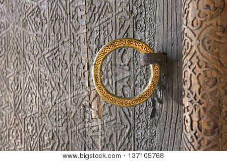 Carved antique door with a gold ring / Vintage Oriental patterns