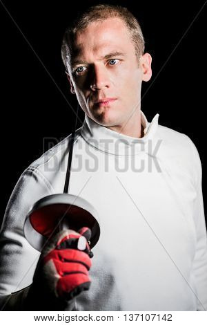 Close-up of swordsman holding fencing sword on black background