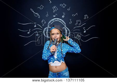 Happy little girl singing a song with microphone over musical background. Studio shot.