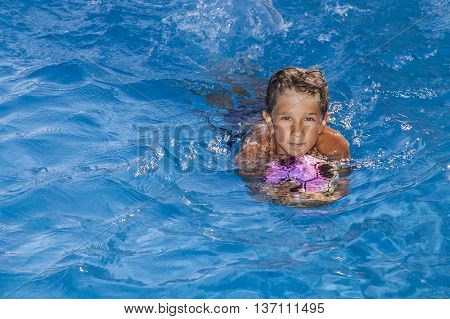 The boy swims in the pool with a ball