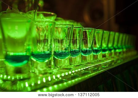 Several shot glasses with cocktail nearby on dark background