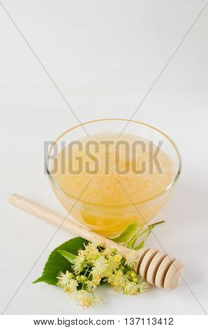 Natural linden honey in a transparent bowl and branch linden blossom on a white wooden background. Folk, alternative, complementary medicine, traditional medicine.