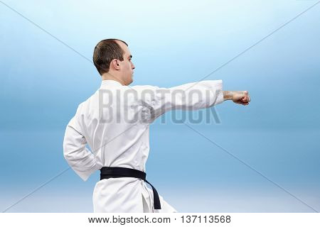 Young sportsman is beating kick gyaku-tsuki on light background