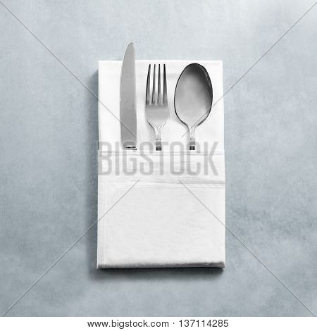Blank white restaurant napkin mock up with knife fork and spoon, isolated. Cutlery in clear textile towel mock up template. Cafe branding identity clean napkin surface for logo design.