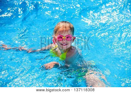Portrait of child wearing googles girl on water in swimming pool . Children's healthy lifestyle into blue water. Summer holiday. Outdoor.