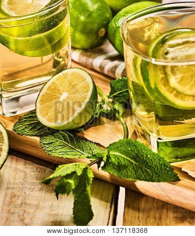 Alcohol drink. On wooden board couple of glasses with alcohol green mohito drink. A mint drink number twenty two mojito cocktail with half lime and napkin. Country life. Light background.