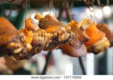 Pork knuckle smoked and cooked lardy meat with bone hang in storage