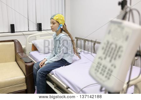 patient girl on procedure of removing of electroencephalogram, sitting on bed looking down