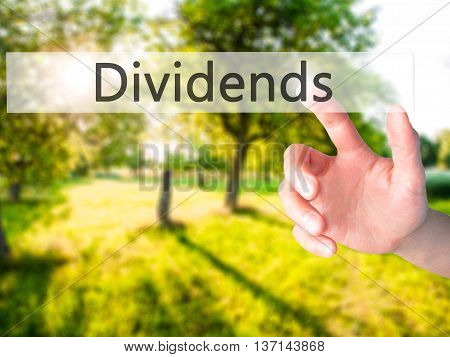 Dividends - Hand Pressing A Button On Blurred Background Concept On Visual Screen.