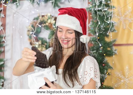 lovely woman with elegant style in Santa cap standing near door of house sham and holding large bar of chocolate, read label on packaging