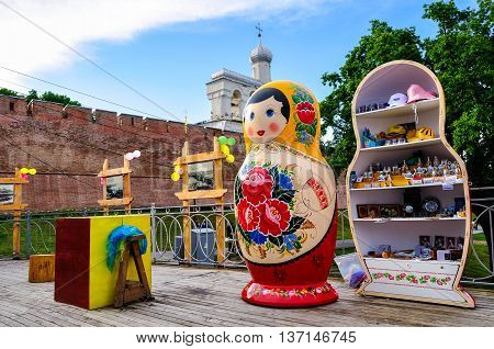 VELIKY NOVGOROD RUSSIA -JUNE 11 2016. Architecture view - Belfry of St Sophia cathedral with big colorful Russian doll matrioshka on the foreground and souvenirs in Veliky Novgorod Russia