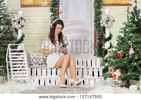 Full portrait of young woman sitting on threshold of fake home and select music track in phone. Christmas interior studio