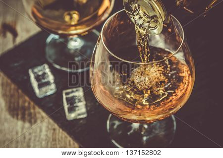 Pouring cognac in a glass, rustic background, toned