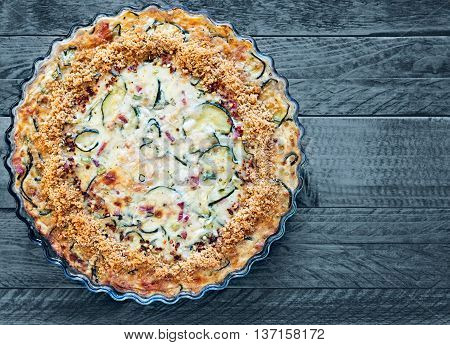 Homemade crustless zucchini quiche baked in a glass fluted dish on a steel blue wooden background