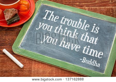 The trouble is you think that you have time- inspirational quote by Buddha  on a slate blackboard with chalk and cup of tea