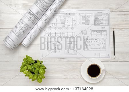Drawing sketches, cup of coffee and houseplant are on wooden surface. Top view compositin. Workplace of architect or constructor. Engineering work. Construction and architecture. Architect drawing. Exact calculation. Office workplace. Increase working eff
