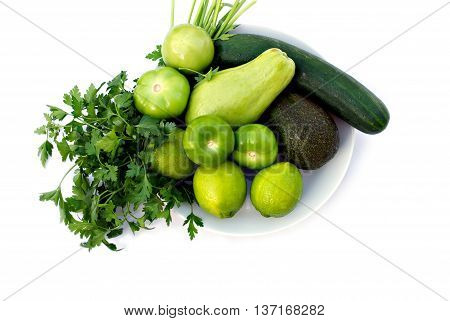 A plate with fresh green vegetables on white background