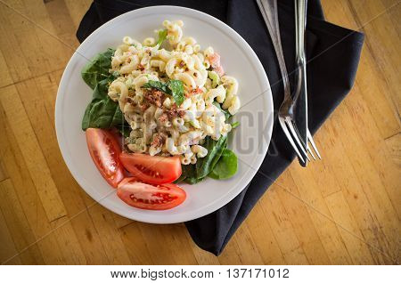 Macaroni salad on bed of spinach greens with tomato wedges and bacon bits poster