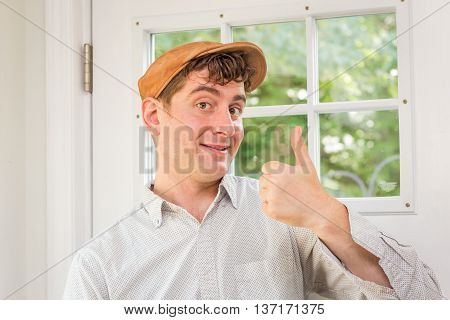 Young handsome curly haired man wearing newsboy hat making thumbs up hand sign