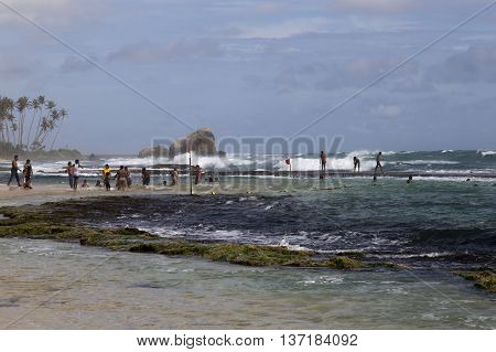 The coast having a rest and swiming people on the religious holiday Vap Poya on Sri Lanka