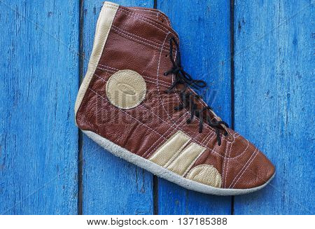 Retro shoes athlete in wrestling on a wooden blue background