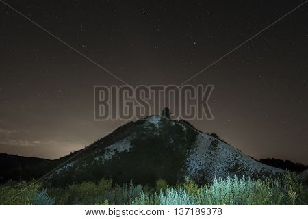 Summer night sky over the white chalky mountain, hill. Starry night landscape. Night background.