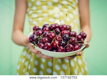 Girl on a background of turquoise wall holding a plate with cherry. Space for text