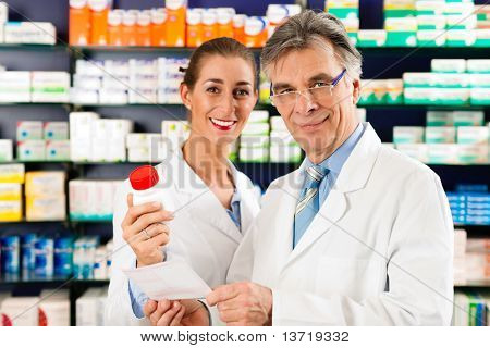Dois farmacêuticos com fármacos na mão consultoria uns aos outros em uma farmácia