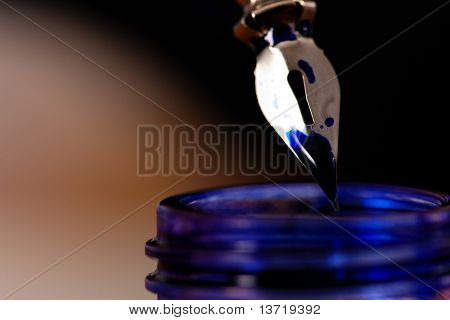 dipping a pen into an ink pot to write a letter