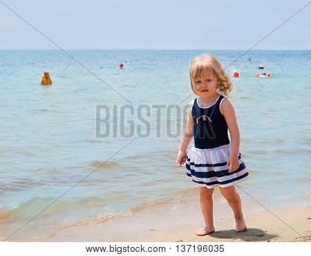 Little beautiful blonde girl baby in the blue sea dress is walking on the beach sand on the beachside people swim in the sea