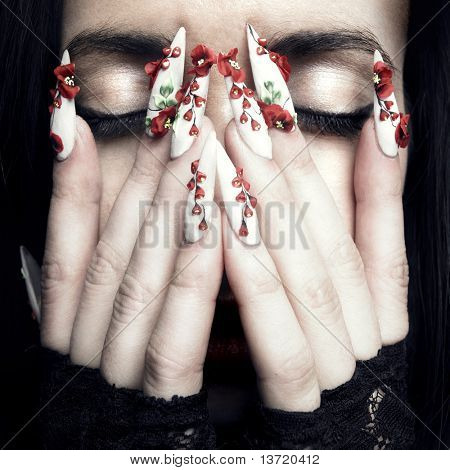 Portrait of a beautiful young woman with long designer nails