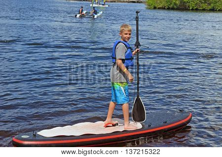Twelve year old boy on a paddle board in the st.lucie river,port st.lucie florida
