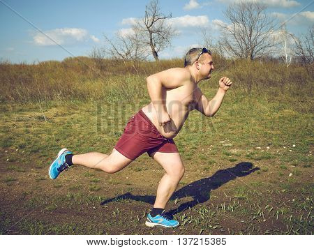 Fat Man Running Outdoors On Nature.