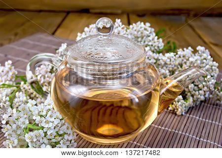 Tea With Yarrow In Glass Teapot On Bamboo