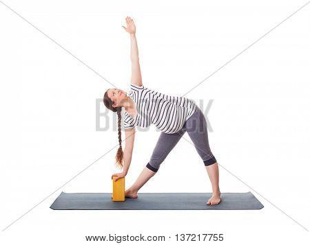 Pregnancy yoga exercise - pregnant woman doing asana Utthita trikonasana - extended triangle pose with block isolated on white background