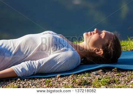 Woman relaxes in yoga relaxation asana Savasana - corpse pose outdoors in Himalayas. Himachal Pradesh, India